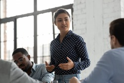 Indian businesswoman negotiates with clients showing persuasion skills during formal meeting feels confident. Business coach provide helpful information at workshop. Negotiations, leadership concept