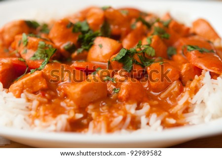 Indian butter chicken sauce with rice and sliced carrots