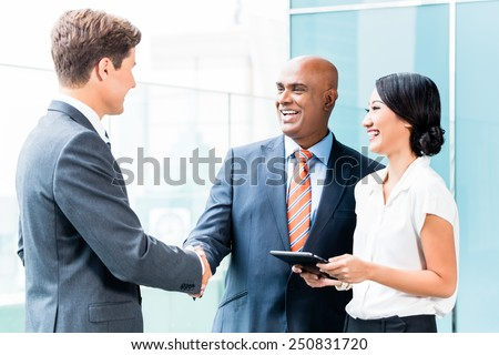 Indian CEO and Caucasian executive having business handshake in front of city skyline