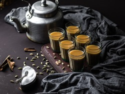Indian chai in glass cups with metal kettle and other masalas to make the tea.