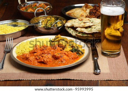Indian chicken curry meal with beer