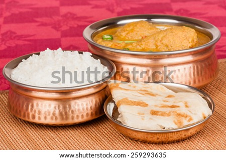 Indian chicken curry meal with rice & parotta (Indian bread) served in authentic copper utensils. Green chilli used as garnish.