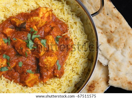 Indian chicken curry with rice and naan bread.