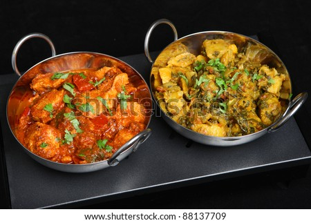 Indian chicken curry with saag aloo (spinach and potato) vegetable curry on traditional restaurant food warmer.
