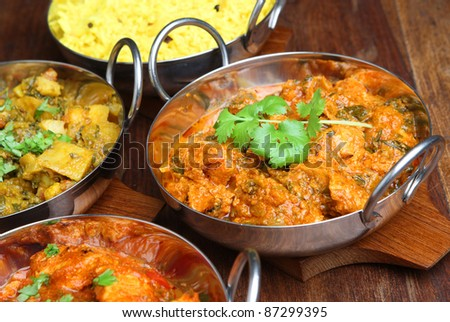 Indian chicken saag massala curry with vegetable curry and rice.