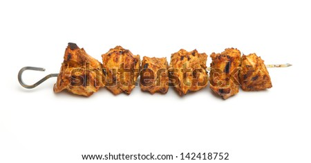 Indian chicken tikka kebab on metal skewer.