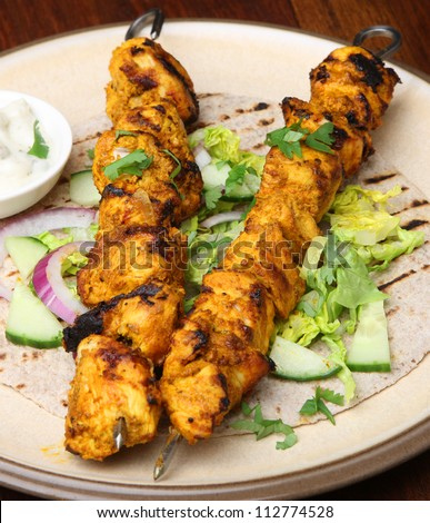 Indian chicken tikka kebabs with chapatti, salad and raita dip. Shallow DoF.