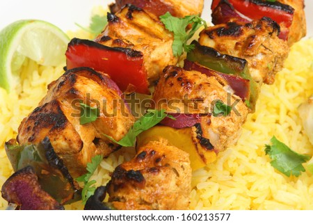 Indian chicken tikka kebabs with red onions and peppers.