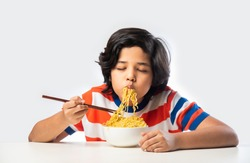 Indian child eating delicious noodles with Fork against White Background, Asian boy eats Spaghetti in a bowl against white background