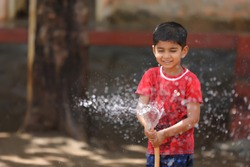 indian child playing with water tube