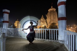 Indian classical Odissi dancer dance recital against the backdrop of at Lingaraja Temple with circle of light painting behind.