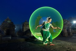 Indian classical Odissi dancer dance recital against the backdrop of at Mukteshvara Temple sculpture light painting behind.