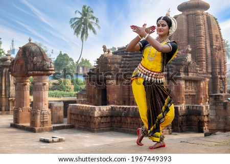 Indian classical Odissi dancer posing in front of 10th century Mukteshvara temple. Odissi dance is a major ancient Indian traditional dance form originated in the Hindu temples of Odisha. Сток-фото ©