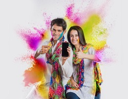 indian couple busy on smartphone on Holi festival, with face painted with colours, and colour splash all over
