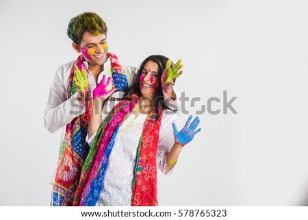 Indian Couple showing their colored hands on Holi festival, isolated over white background #578765323