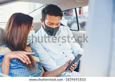 Indian couple wearing face medical masks taking a cab and using mobile phone app for booking Foto stock ©
