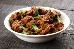 Indian cuisine- Bowl of tasty mutton roast with Indian spices .Selective focus photograph.