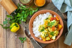 Indian cuisine dish sabji. Traditional Indian vegetable stew with soft cheese and turmeric on a wooden table. Top view flat lay background.