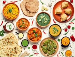 Indian cuisine dishes: tikka masala, dahl, paneer, samosa, chapati, chutney, spices. Indian food on white wooden background. Assortment indian pakistani meal top view or flat lay.