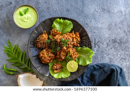 Indian cuisine. pakora traditional Indian deep-fried snack. pakoras on black plate with coconut chutney sauce curry leaves. national appetiser authentic vegetarian food. Asian travel food. top view. Stock photo ©