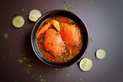 Indian Cuisine, Spicy Crabs Curry or chimbori or khekde in red gravy, garnished with fresh coriander and lemon wedges or lemon slices on dark moody background
