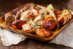 Indian cuisine tandoori oven baked platter of appetizers including malai tikka chicken kebabs shrimp and seekh kebab