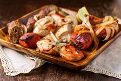 Indian cuisine tandoori oven baked platter of appetizers including malai tikka chicken kebabs shrimp and seekh kebab