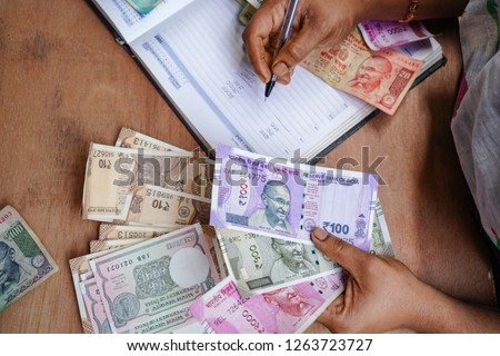 indian Currency (Rupee) 2000,500,100,50,10,1Rupee.   Close up of female accountant or banker making calculations