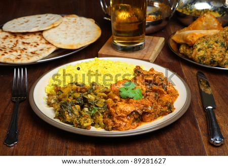 Indian curry meal with naan and lager.
