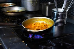 Indian curry style dishes being prepared in a commercial restaurant kitchen.