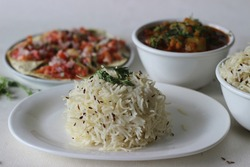 Indian dish made of basmati rice flavoured with cumin seeds and spices. Locally known as jeera rice served with Bottle Gourd Curry with Lentils and Crisp and fried papads topped with masala filling
