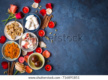 Indian Diwali celebratory background with traditional sweets. Gulab jamun, carrot halwa, snacks with candles, flowers. Assorted indian desserts. Holiday festive table. Diwali setting. Space for text