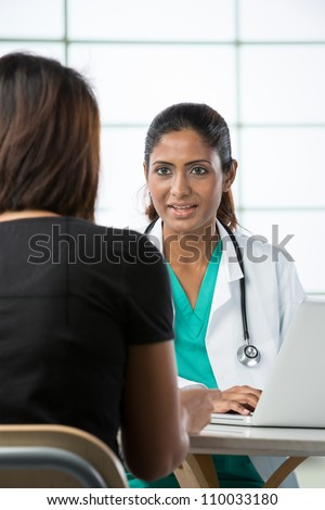 Indian doctor talking with female patient in doctors office. - stock photo