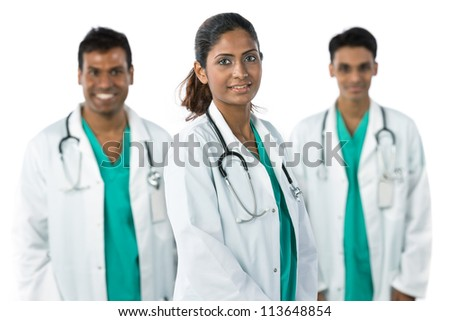 Indian doctor wearing a white coat with stethoscope. Her team are out of focus in background.
