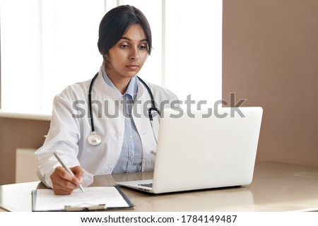Indian ethnic female doctor gp wearing white coat stethoscope writing watching online medical webinar seminar training or virtual meeting remote patient by video call working on laptop at workplace.