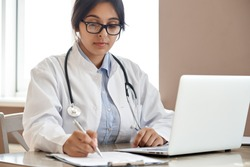 Indian ethnic female doctor physician gp wearing glasses, white coat stethoscope writing filling medical form watching online medical webinar seminar training working sitting with laptop at workplace.