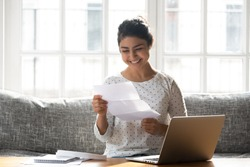Indian ethnicity woman sitting on couch at home reading paper notice receive good news feels happy, cheerful student female looking at document enjoy exam results or college admission letter concept