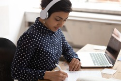 Indian ethnicity woman wearing headphones listens educational course writing down necessary useful information gain knowledge online use internet lesson, interpreter do translation sit at desk indoors
