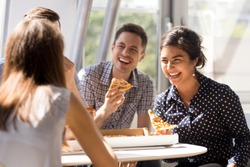 Indian excited woman laughing at funny joke, eating pizza with diverse colleagues in office, happy multi-ethnic employees having fun together during lunch, enjoying good conversation, emotions