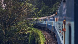 Indian express train running through the green forest over a bridge in Konkan route.
