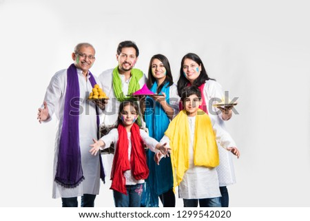 indian family celebrating holi festival with sweet laddu gifts and colours in plate. isolated over white background. selective focus meaning