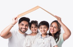 Indian family Father, mother, son and daughter holding 3D paper model of home - Real Istate Concept in India