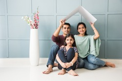 Indian family Father, mother, son and daughter holding House roof made of cardboard - Real Istate Concept in India