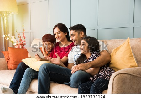 Indian family sitting on sofa and using smartphone, laptop or tablet, watching movie or surfing internet