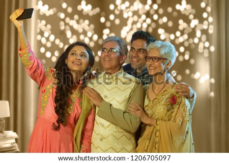 Indian family taking selfie or self photograph at home on diwali festival