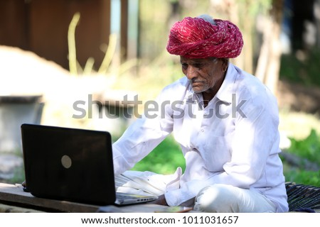 Indian farmer working on Laptop. Modern farmer of India. Tech Savvy Indian Grandpa. Indian Grandpa loves playing with laptop. Technology reaches rural India.Which laptop to buy for Seniors.   #1011031657
