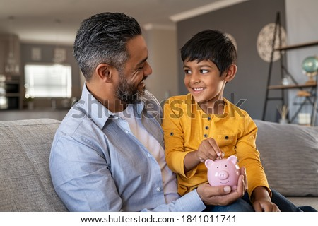 Indian father and smiling son putting coin into piggy bank. Smiling boy sitting on father lap saving money in piggybank. Middle eastern dad teaching son to save money while putting coin in piggy bank.