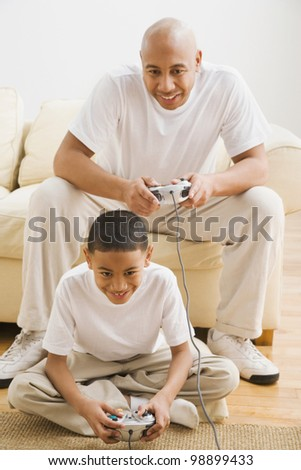 Indian father and son playing video games - stock photo