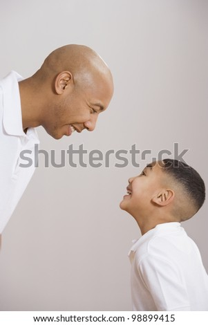 Indian father and son smiling at each other