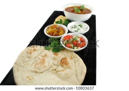 Indian feast of vindaloo curry, naan bread, mango chutney, banana and ...